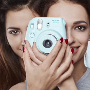 Studio lifestyle portrait of two best friends hipster crazy girls with polaroid wearing stylish bright outfits